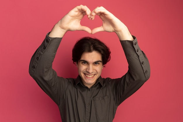 Uśmiechnięty młody przystojny facet na sobie czarną koszulkę pokazując gest serca na białym tle na różowej ścianie