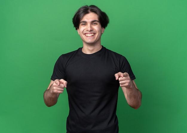 Uśmiechnięty młody przystojny facet na sobie czarną koszulkę pokazuje gest na białym tle na zielonej ścianie