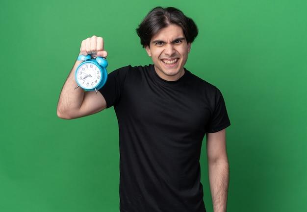 Uśmiechnięty młody przystojny facet na sobie czarną koszulkę, trzymając budzik na białym tle na zielonej ścianie