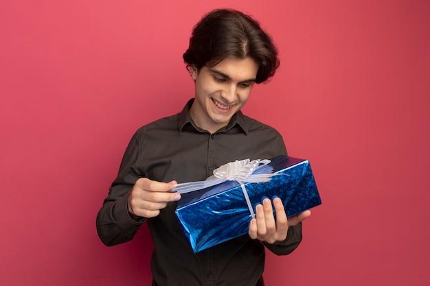 Uśmiechnięty młody przystojny facet na sobie czarną koszulkę, trzymając i patrząc na pudełko na białym tle na różowej ścianie
