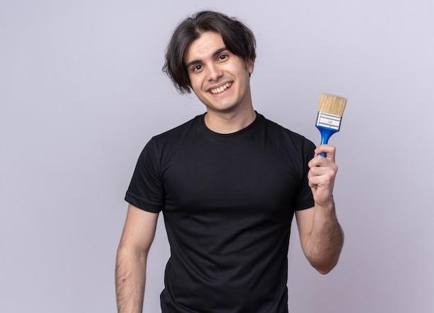 Uśmiechnięty młody przystojny facet na sobie czarną koszulkę, trzymając pędzel na białym tle na białej ścianie