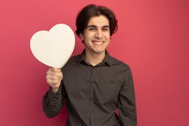 Uśmiechnięty młody przystojny facet na sobie czarną koszulkę, trzymając pudełko w kształcie serca na białym tle na różowej ścianie