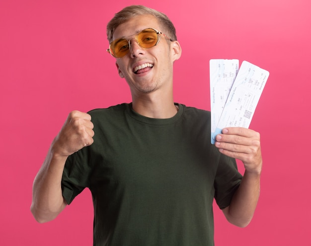 Uśmiechnięty młody przystojny facet na sobie zieloną koszulę i okulary trzymając bilety pokazujące tak gest na białym tle na różowej ścianie