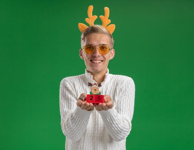 Uśmiechnięty młody przystojny facet noszący opaskę z poroża renifera w okularach trzymający zabawkę choinkową z datą wyglądającą odizolowaną na zielonej ścianie z kopią przestrzeni