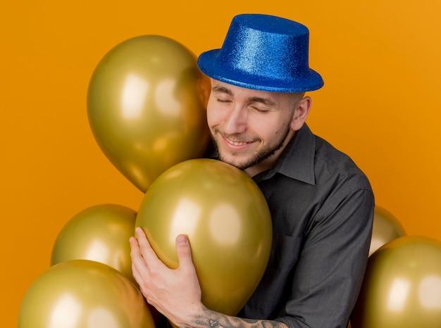 Uśmiechnięty młody przystojny facet słowiańskich partii na sobie kapelusz partii stojącej wśród balonów chwytając jeden z zamkniętymi oczami na białym tle na pomarańczowym tle