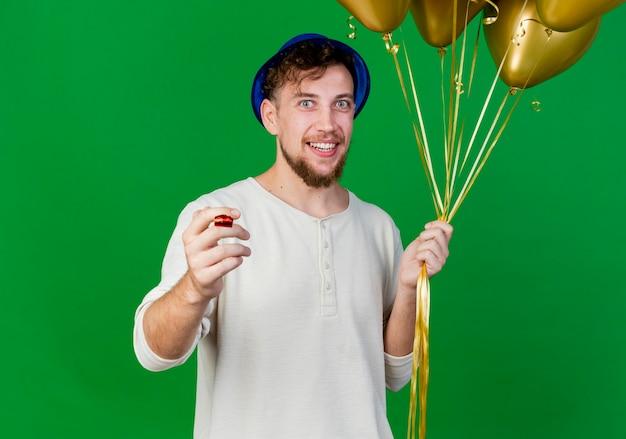 Uśmiechnięty młody przystojny facet słowiańskich partii na sobie kapelusz partii trzymając balony i dmuchawę strony patrząc na kamery na białym tle na zielonym tle z miejsca na kopię