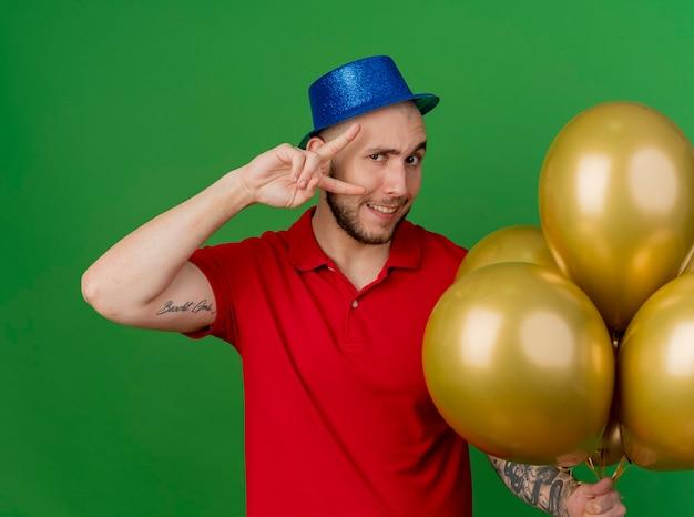 Uśmiechnięty młody przystojny facet słowiańskich partii na sobie kapelusz partii trzymając balony robi znak pokoju patrząc na kamery na białym tle na zielonym tle