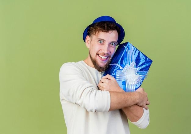 Uśmiechnięty młody przystojny facet słowiańskich partii na sobie kapelusz strony gospodarstwa pudełko, patrząc na kamery na białym tle na oliwkowym tle z miejsca kopiowania