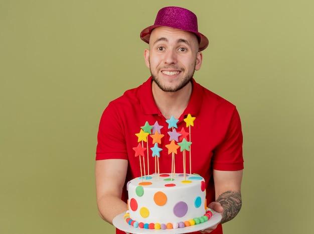 Uśmiechnięty młody przystojny facet słowiańskich partii na sobie kapelusz strony gospodarstwa tort urodzinowy patrząc na kamery na białym tle na oliwkowym tle z miejsca kopiowania