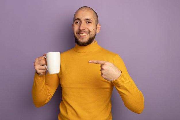 Uśmiechnięty młody przystojny facet trzyma i wskazuje na filiżankę herbaty na białym tle na fioletowej ścianie