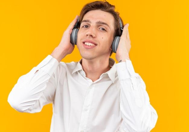 Uśmiechnięty młody przystojny facet ubrany w białą koszulę ze słuchawkami odizolowanymi na pomarańczowej ścianie