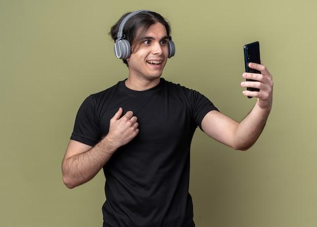 Uśmiechnięty młody przystojny facet ubrany w czarną koszulkę i słuchawki bierze selfie na białym tle na oliwkowej ścianie
