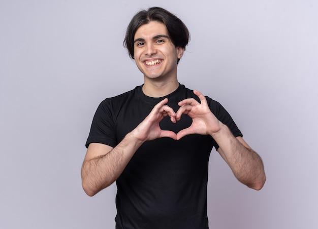 Uśmiechnięty młody przystojny facet ubrany w czarną koszulkę pokazujący gest serca na białym tle na białej ścianie