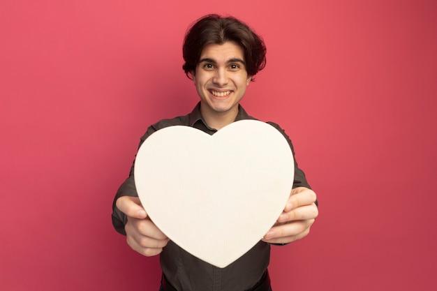 Uśmiechnięty młody przystojny facet ubrany w czarną koszulkę trzyma pudełko w kształcie serca z przodu na białym tle na różowej ścianie