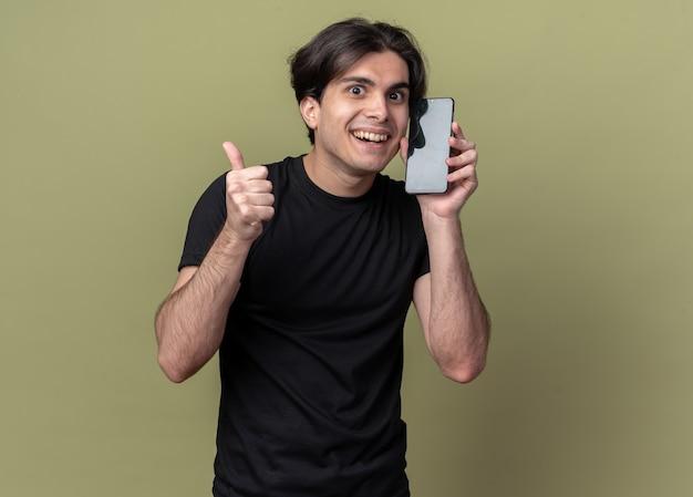 Uśmiechnięty młody przystojny facet ubrany w czarną koszulkę, trzymając budzik wokół twarzy, pokazując kciuk do góry na białym tle na oliwkowej ścianie