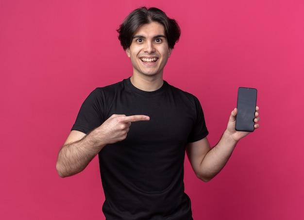 Uśmiechnięty młody przystojny facet ubrany w czarną koszulkę, trzymający i wskazujący na telefon odizolowany na różowej ścianie