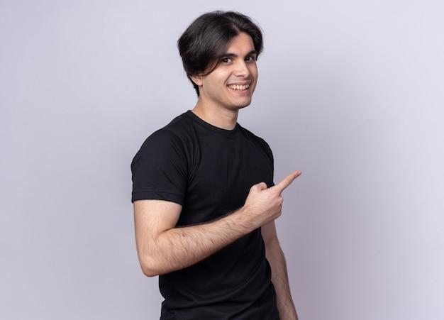Uśmiechnięty Młody Przystojny Facet Ubrany W Czarną Koszulkę Wskazuje Na Bok Na Białym Tle Na Białej ścianie Z Miejsca Na Kopię Darmowe Zdjęcia