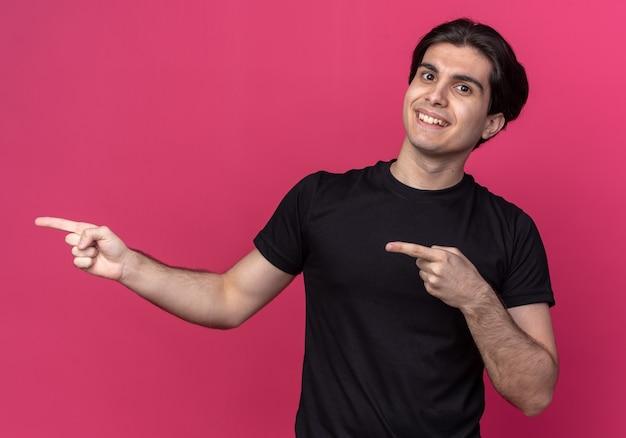 Uśmiechnięty młody przystojny facet ubrany w czarną koszulkę wskazuje na bok na białym tle na różowej ścianie z miejsca na kopię