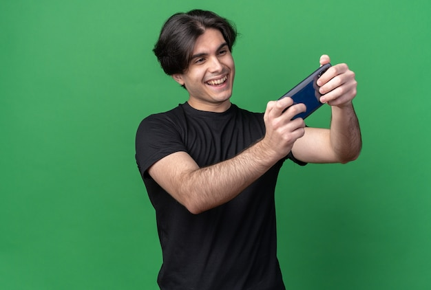 Uśmiechnięty młody przystojny facet ubrany w czarną koszulkę wziąć selfie na białym tle na zielonej ścianie z miejsca na kopię