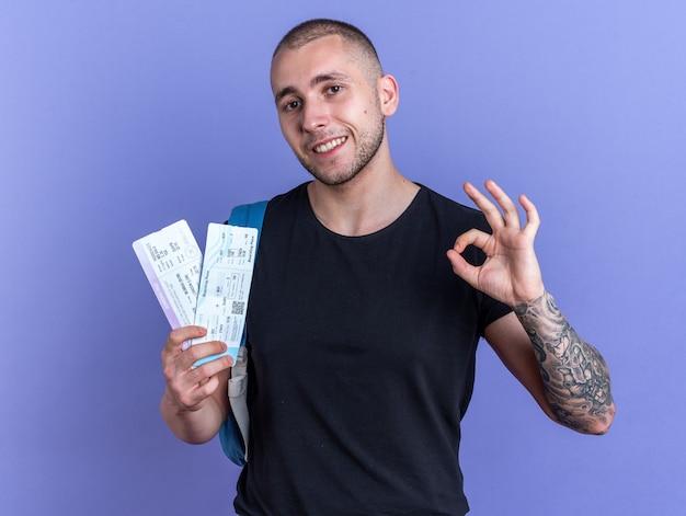 Uśmiechnięty młody przystojny facet ubrany w czarną koszulkę z plecakiem trzymający bilety pokazujące dobry gest na białym tle na niebieskim tle