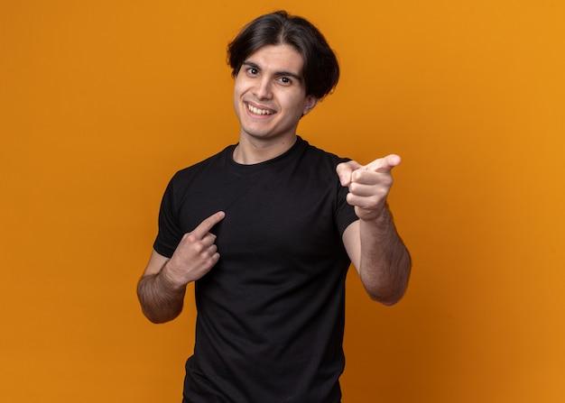Uśmiechnięty młody przystojny facet ubrany w czarny t-shirt wskazuje na bok na białym tle na pomarańczowej ścianie z miejsca na kopię
