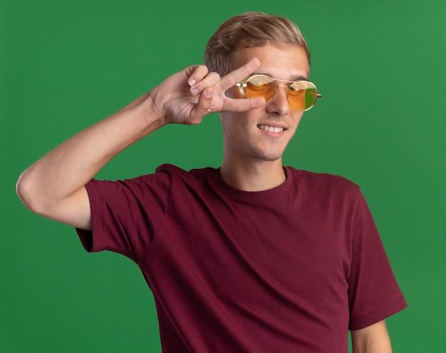 Uśmiechnięty młody przystojny facet ubrany w czerwoną koszulę i okulary pokazujące gest pokoju na białym tle na zielonej ścianie