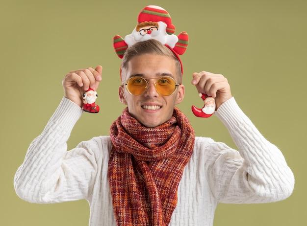 Uśmiechnięty młody przystojny facet ubrany w opaskę świętego mikołaja i szalik patrzący trzymający ozdoby świąteczne świętego mikołaja odizolowanych na oliwkowozielonej ścianie