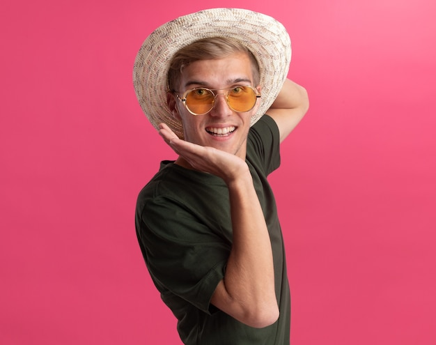 Uśmiechnięty młody przystojny facet ubrany w zieloną koszulę i okulary z kapeluszem, kładący rękę pod brodą na białym tle na różowej ścianie