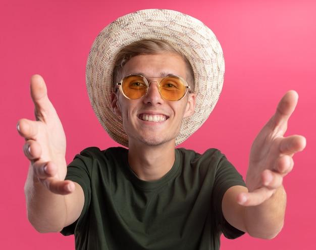 Uśmiechnięty młody przystojny facet ubrany w zieloną koszulę i okulary z kapeluszem wyciągniętym do aparatu na białym tle na różowej ścianie