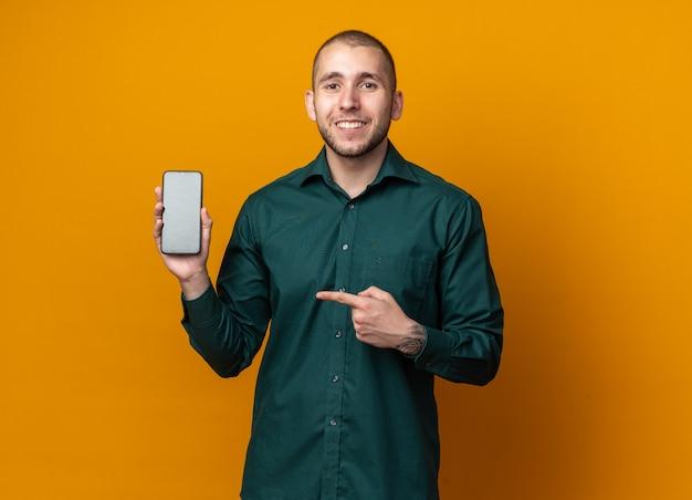 Uśmiechnięty młody przystojny facet ubrany w zieloną koszulę, trzymający i wskazujący na telefon