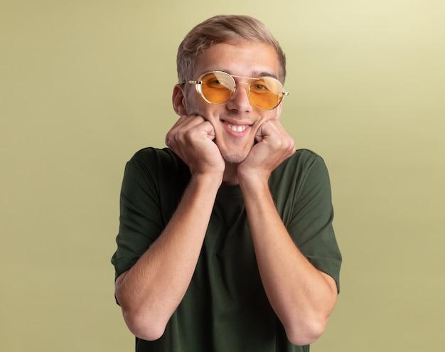 Uśmiechnięty młody przystojny facet ubrany w zieloną koszulę w okularach kładąc pięści na policzkach na białym tle na oliwkowej ścianie