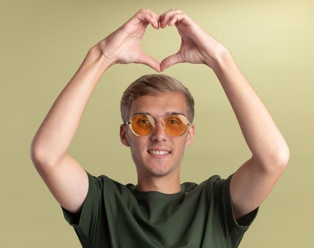 Uśmiechnięty młody przystojny facet ubrany w zieloną koszulę w okularach pokazując gest serca na białym tle na oliwkowej ścianie