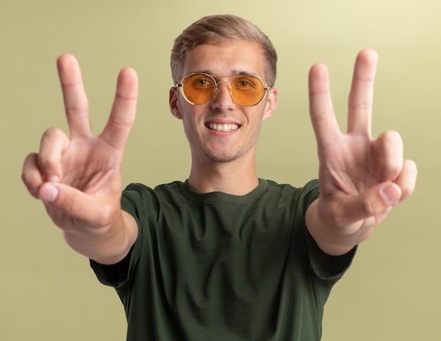 Uśmiechnięty młody przystojny facet ubrany w zieloną koszulę w okularach pokazujących gest pokoju na oliwkowej ścianie