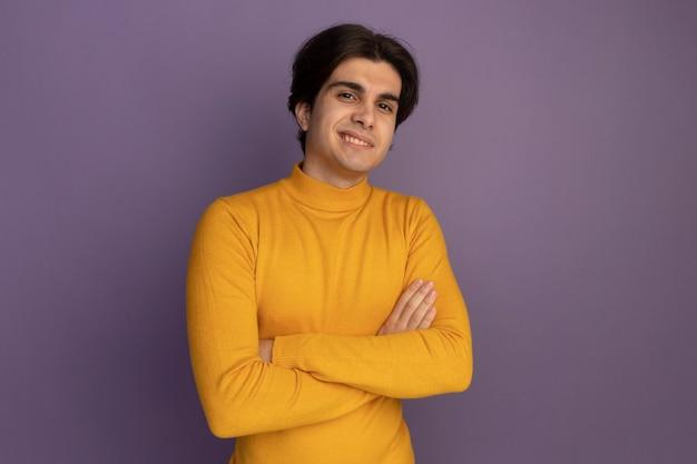Uśmiechnięty młody przystojny facet ubrany w żółty sweter z golfem skrzyżowane ręce na białym tle na fioletowej ścianie z miejsca na kopię