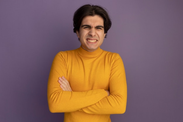 Uśmiechnięty młody przystojny facet ubrany w żółty sweter z golfem skrzyżowane ręce na białym tle na fioletowej ścianie