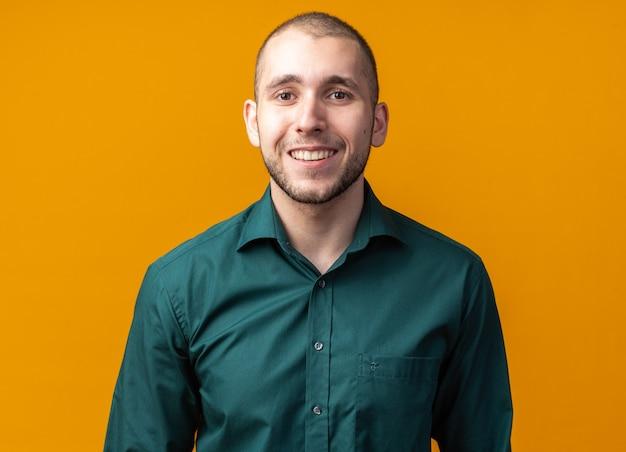 Uśmiechnięty młody przystojny facet w zielonej koszuli