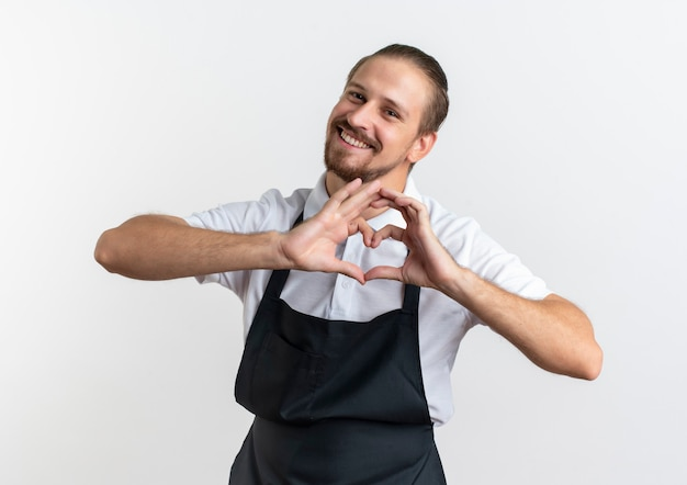 Uśmiechnięty młody przystojny fryzjer na sobie mundur robi znak serca na białym tle na białej ścianie
