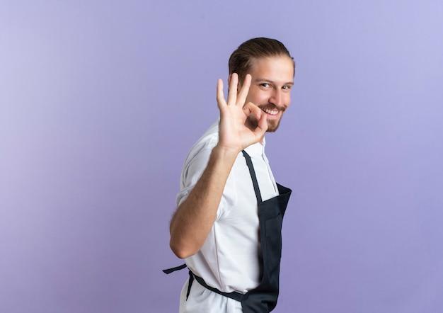 Uśmiechnięty młody przystojny fryzjer na sobie mundur stojący w widoku profilu i robi ok znak na białym tle na fioletowej ścianie