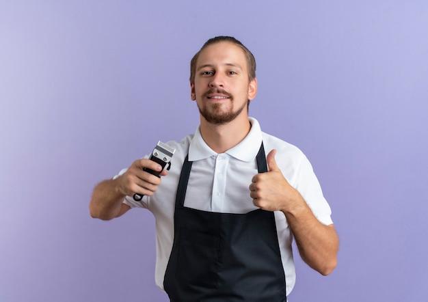 Uśmiechnięty młody przystojny fryzjer na sobie mundur trzymając maszynkę do strzyżenia włosów i pokazując kciuk w górę na białym tle na fioletowej ścianie