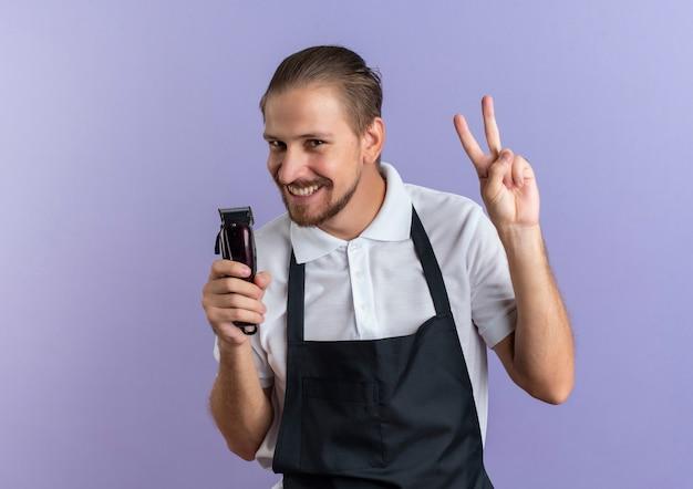 Uśmiechnięty młody przystojny fryzjer na sobie mundur trzymając maszynkę do strzyżenia włosów i robi znak pokoju na białym tle na fioletowej ścianie