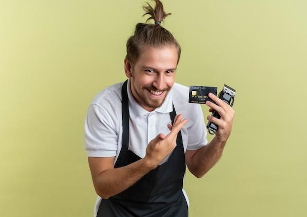 Uśmiechnięty młody przystojny fryzjer trzymając i wskazując ręką na kartę kredytową i maszynki do strzyżenia włosów na białym tle na oliwkowej ścianie