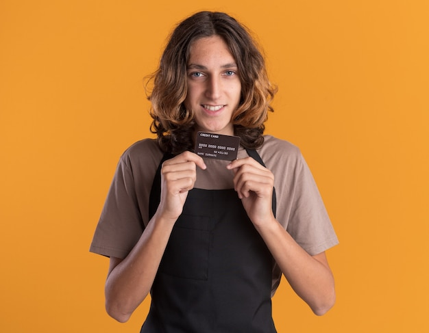 Uśmiechnięty młody przystojny fryzjer ubrany w mundur pokazujący kartę kredytową do aparatu na białym tle na pomarańczowej ścianie
