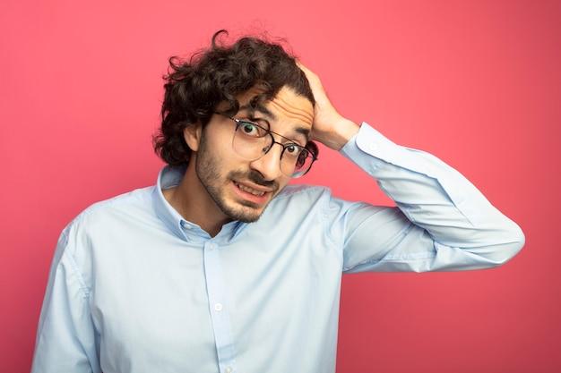 Uśmiechnięty młody przystojny kaukaski mężczyzna w okularach patrząc na kamery kładąc rękę na głowie na białym tle na szkarłatnym tle
