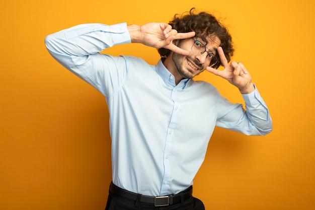 Uśmiechnięty młody przystojny kaukaski mężczyzna w okularach patrząc na kamery, trzymając ręce w pobliżu oczu robi znak pokoju na białym tle na pomarańczowym tle