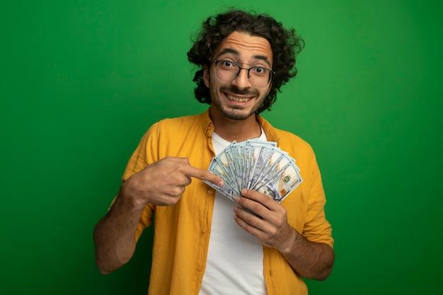 Uśmiechnięty młody przystojny kaukaski mężczyzna w okularach, trzymając i wskazując na pieniądze patrząc na kamery na białym tle na zielonym tle z miejsca na kopię