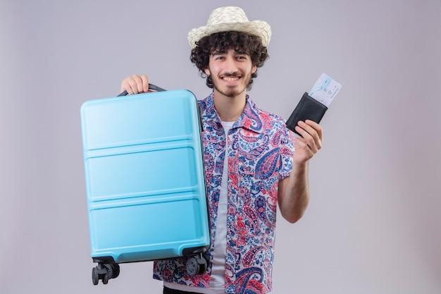 Uśmiechnięty młody przystojny kręcone podróżnik mężczyzna w kapeluszu, trzymając portfel i bilety lotnicze i walizkę na na białym tle białej ścianie z miejsca na kopię