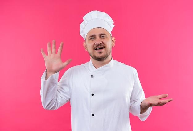 Uśmiechnięty młody przystojny kucharz w mundurze szefa kuchni pokazuje puste ręce na białym tle na różowej przestrzeni