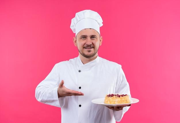 Uśmiechnięty młody przystojny kucharz w mundurze szefa kuchni, trzymając i wskazując na talerz ciasta na białym tle na różowej przestrzeni