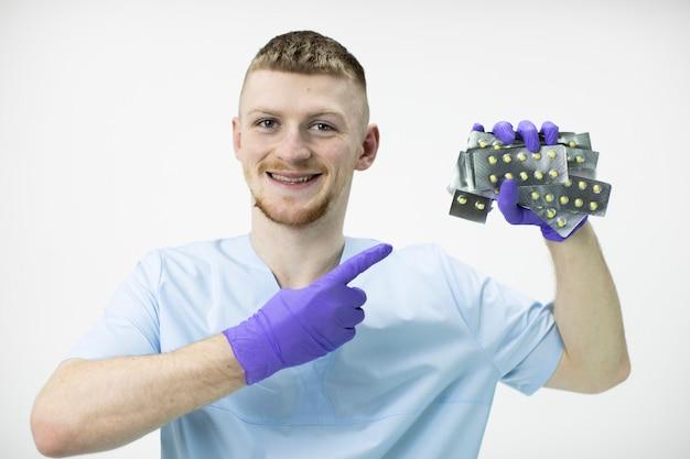 Uśmiechnięty młody przystojny lekarz posiada wiele blistrów wskazuje na nich z wesołym wyrazem twarzy