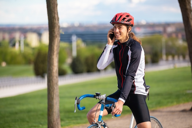 Uśmiechnięty młody przystojny męski cyklista w sportswear i ochronnym hełmie na rowerowym mówieniu na telefonie w miasto parku